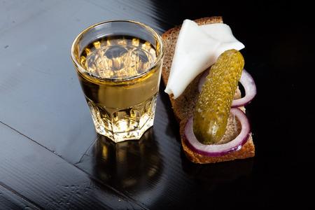 Russische wodka in kleine glazen met zwarte brood, gebeitst, ui en beetje reuzel op een witte achtergrond