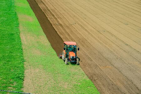 The scenery which cultivates the field with the tractor