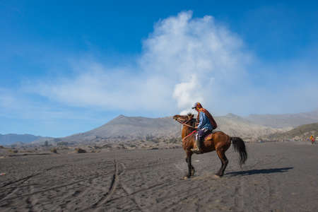 BROMO, INDONESIA - SEP 13: Unidentified worker sitting horse rental provide for tourists at Mount Bromo on SEP 13, 2015 in Java, Indonesia. Mount Bromo is one of the most visited tourist attractions Éditoriale