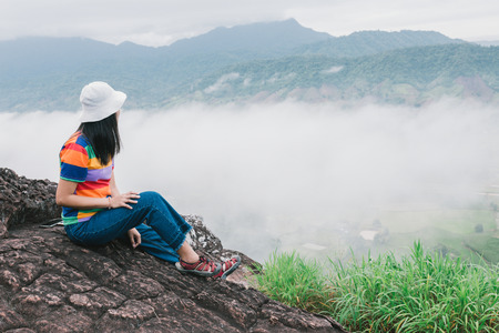 Young woman with backpack sitting on a cliff and enjoying a foggy view Banque d'images