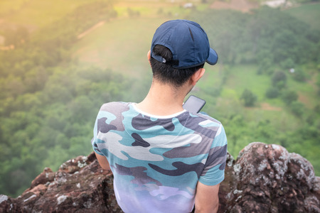 Man Traveler playing mobilephone and sitting on cliff bridge edge with forest aerial view Travel Lifestyle adventure vacations concept