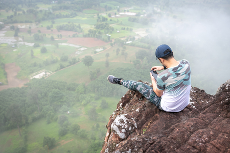 The man watching mobile phone and sitting on the cliff.