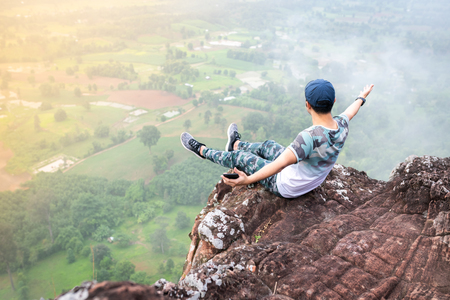 The man raise two hand up and sitting on the cliff. Banque d'images