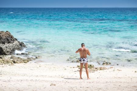 Man relaxing on exotic beach  in Mai Thon Island, Phuket, Thailand