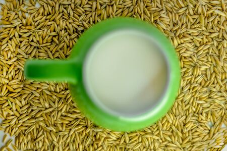 green mug with milk. healthy eating. good food. delicious drink. oat milk. Suitable for writing articles about diet, oat products, recipes. white background, scattered oat seeds.