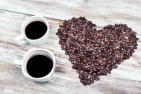 twee kopjes koffie met bonen in de vorm van het hart