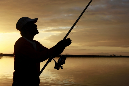 A silhouette of a fisherman holding a fishing rod photo