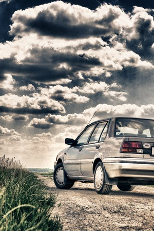 nissan: car on the road under a cloud Editorial