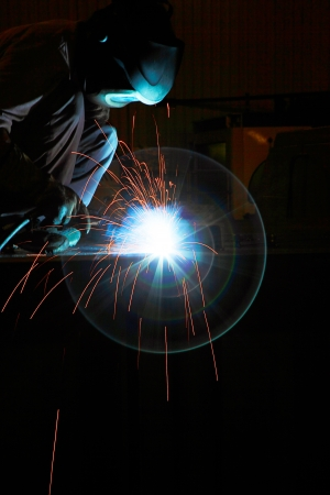 Worker with protective mask weld metal in industrial environment and sparks spread photo