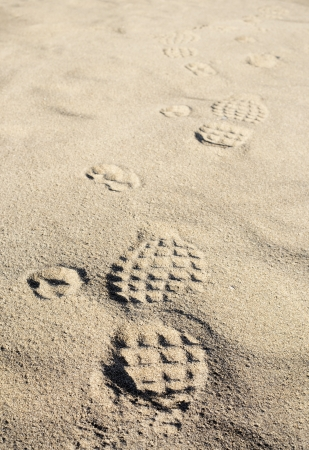 Dog and human footmarks on sand  photo