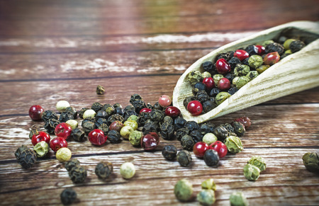 peppercorns: Mixed dried peppercorns on a wooden spoon.