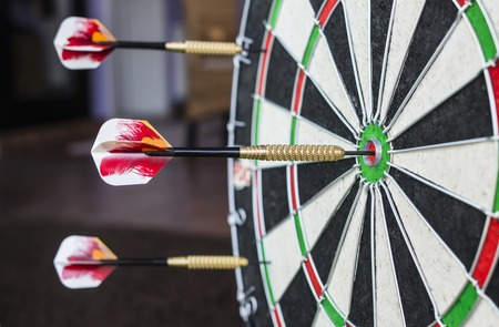 dart on target: A dartboard close-up with a bullseye hits. Stock Photo