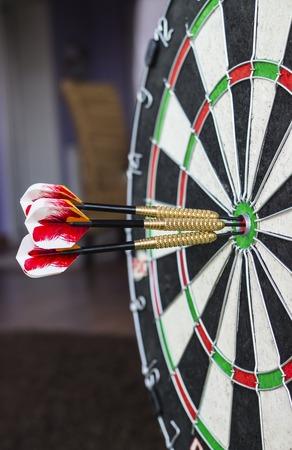 dartboard: A dartboard close-up with three bullseye hits.