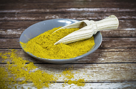 small plate: Small plate of curry powder with wooden spoon Stock Photo