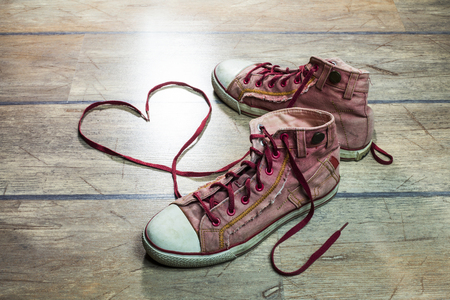 teenager girl: Used, dirty sneakers, with heart shaped shoelaces on a wooden floor.