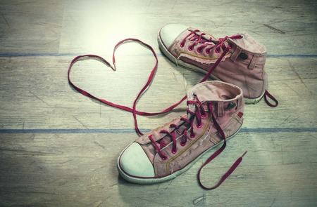 of boy and girl: Used, dirty sneakers, with heart shaped shoelaces on a wooden floor.