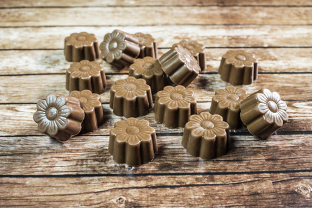 Some chocolates still life on wooden background.
