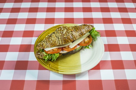 Seedy croissant sandwich on a checkered tablecloth.