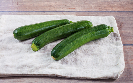 Some fresh, young zucchini on linen tablecloth.