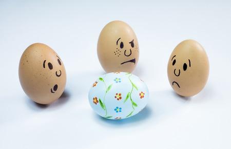 caras de huevo son alrededor de un huevo de Pascua.