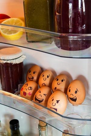 Funny egg faces in a fridge door.