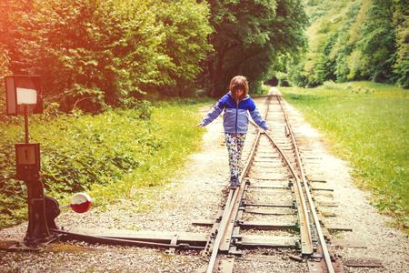 A little girl balancing on the rails. Zdjęcie Seryjne