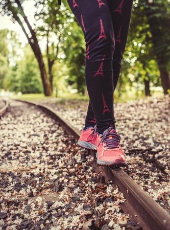 A girl in sneakers, balancing on rail. Zdjęcie Seryjne