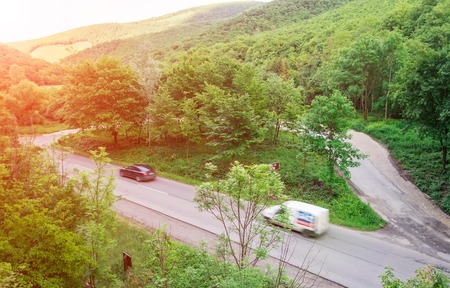 A forest road from hillside view with two cars.
