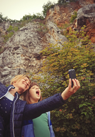 Mother and daughter taking selfie in nature.
