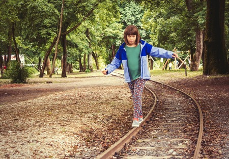 A little girl balancing on the rails. Zdjęcie Seryjne
