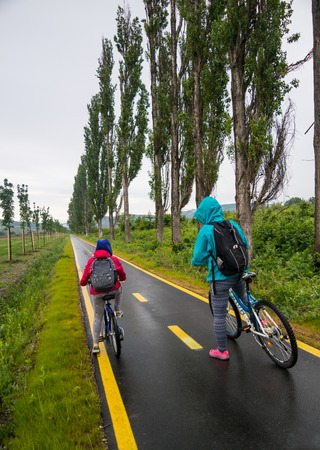 Mother and daughter ride in the cycleway.