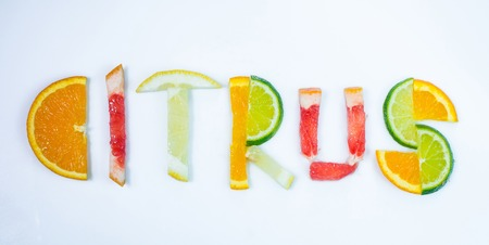 CITRUS word composed of different citruses on white background.