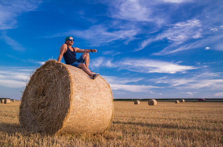 A man resting on a wheat straw bale. Publikacyjne
