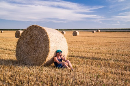 A man resting beside a wheat straw bale.