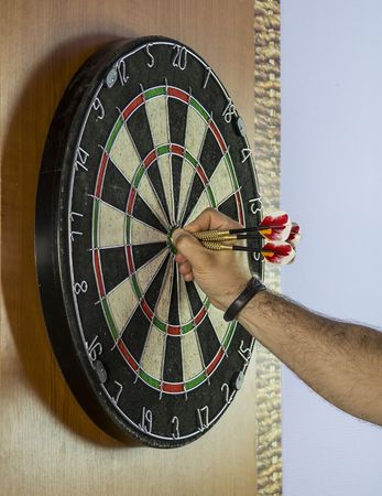 Hand pulling out three darts from a dart board.