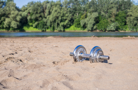 One-handed iron dumbbell on a sandy beach.