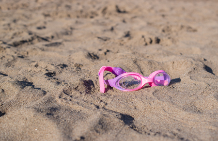 A pink swimming goggles on the sandy beach.