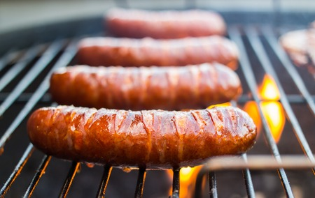 Fried pork sausages on a grill grid.