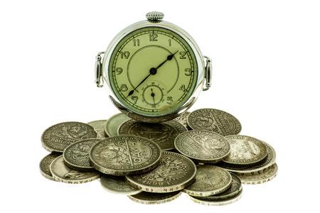monete antiche: Vecchie monete e orologio da tasca su uno sfondo bianco.