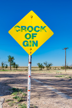 restlessness: ADRIAN, TEXAS USA - MAY 8, 2013  Whimsical  Crock of Gin  mock traffic sign, part of the  Dynamite Museum  art project, on Route 66  Patron  Stanley Marsh 3 Editorial