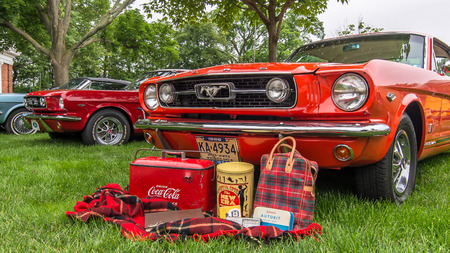 muster: DEARBORN, MIUSA - JUNE 20, 2015: Three Ford Mustang cars, including a 1966 Mustang GT, at The Henry Ford THF Motor Muster, held at Greenfield Village.