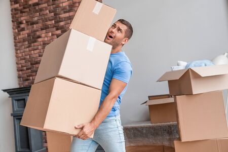 Younf man trying to carry all the boxes for fun while moving
