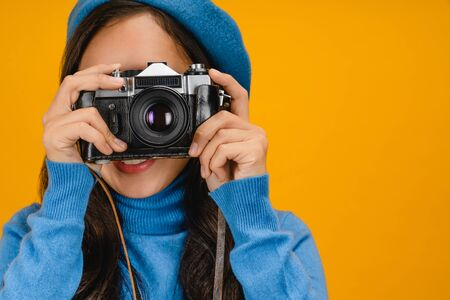 Close up portrait of smiling pretty girl in blue sweater taking photo on retro camera isolated over yellow background