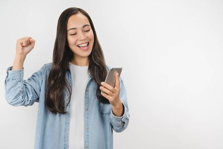 Happy satisfied asian girl in casual wear holding mobile phone isolated over white background