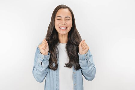 Portrait of young emotional asian girl laughing with closed eyes over white background
