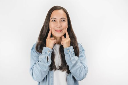 Young asian woman smiling with fingers pointing and forcing cheerful smile standing over white isolated background