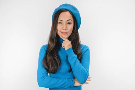 Portrait of cute thinking young french woman in beret posing isolated over white background