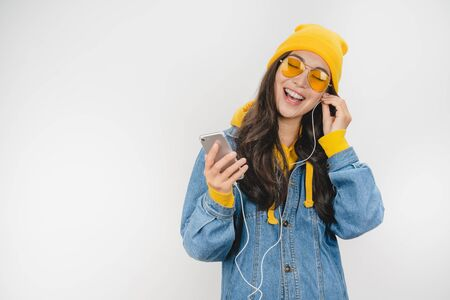 Image of young woman posing isolated over white background listening music with earphones using mobile phone