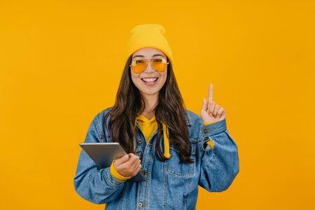 Emocionada mujer asiática sosteniendo tableta digital y apuntando con el dedo hacia arriba en el espacio de la copia mientras está de pie aislado sobre fondo amarillo
