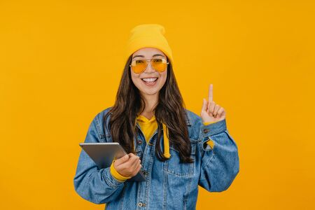 Excited asian woman holding digital tablet and pointing finger up at copy space while standing isolated over yellow background